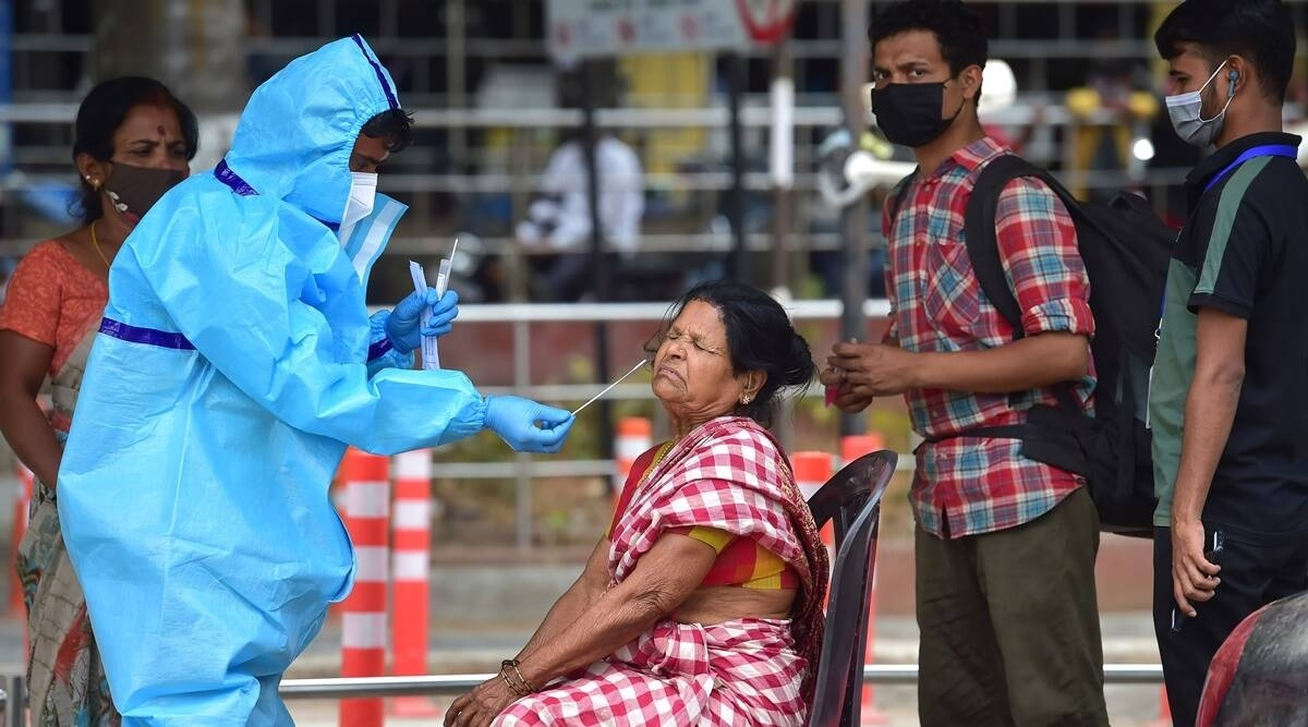A healthcare worker collects a swab sample at the Bengaluru City Railway Station.