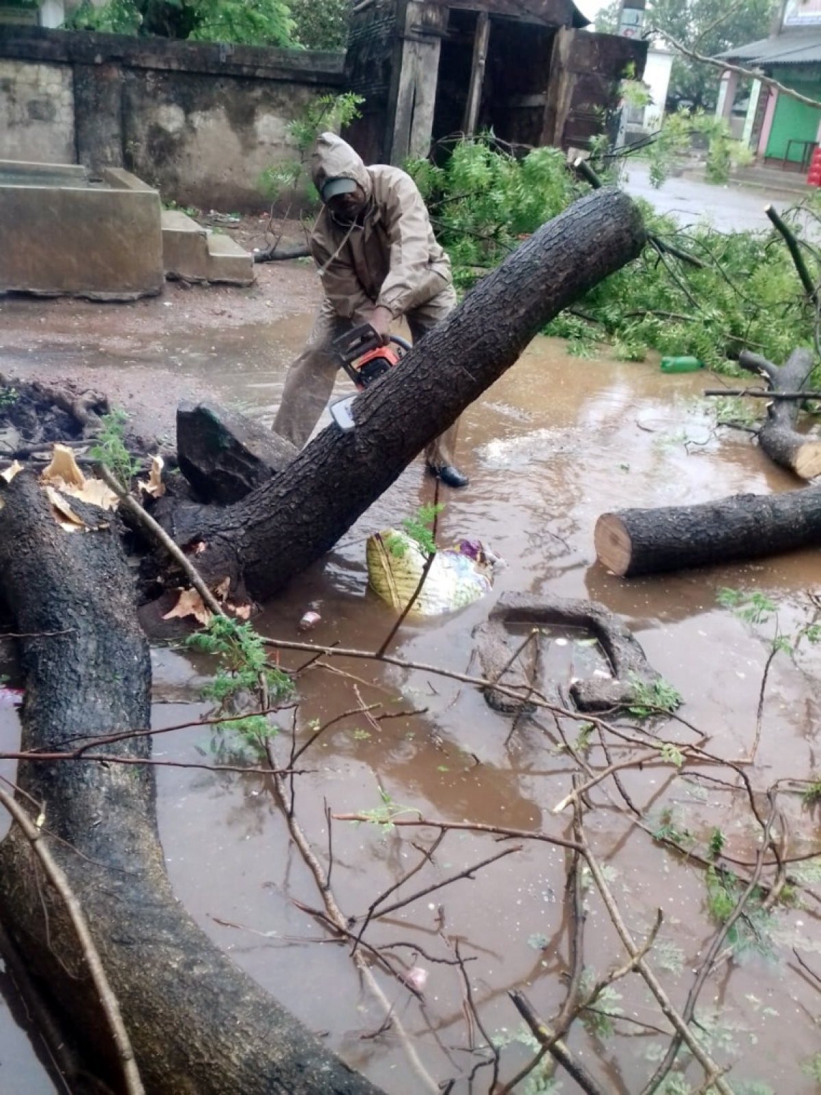 Firefighters personnel clear a fallen tree from a road as they carry out restoration works in the aftermath of Cyclone Yaas