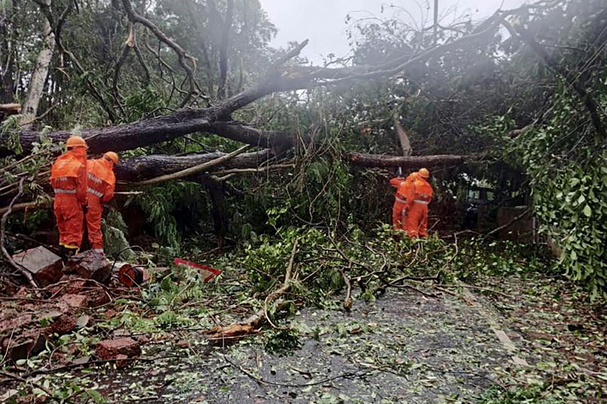 This handout photo released on May 16, 2021 by the National Disaster Response Force (NDRF) shows National Disaster Response Force (NDRF) personnel clearing fallen trees from a road following severe cyclonic storm Tauktae at Margao in Goa.