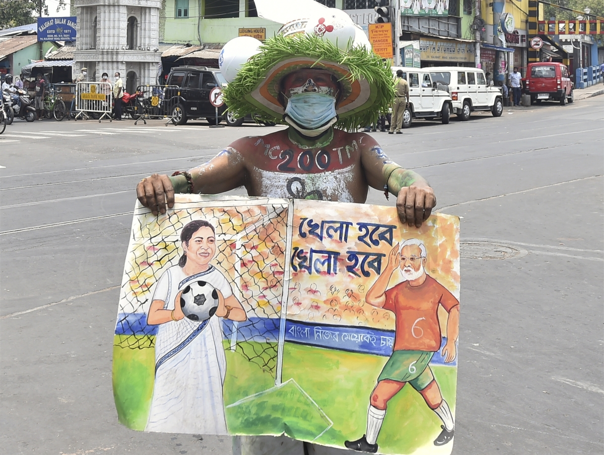 Kolkata: A TMC supporter holds a placard outside West Bengal Chief Minister Mamata Banerjees residence at Kalighat during the counting of West Bengal Assembly poll, as the state government observes a shutdown to combat the Covid-19 situation, no gathering and rallies are strictly prohibited in this situation in Kolkata, Sunday, May 2, 2021.