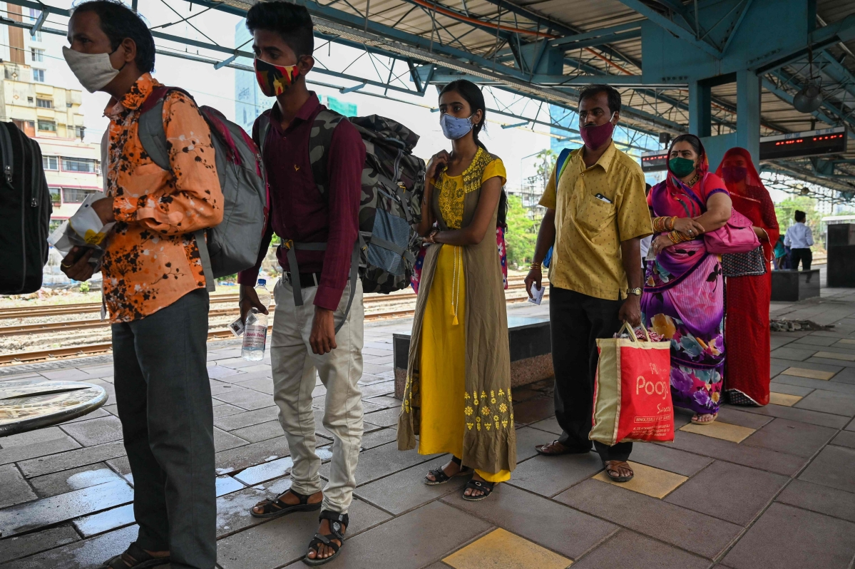 Passengers queue up to give a nasal swab sample for a Covid-19 coronavirus test after arriving at a railway platform on a long distance train, in Mumbai on May 27, 2021.