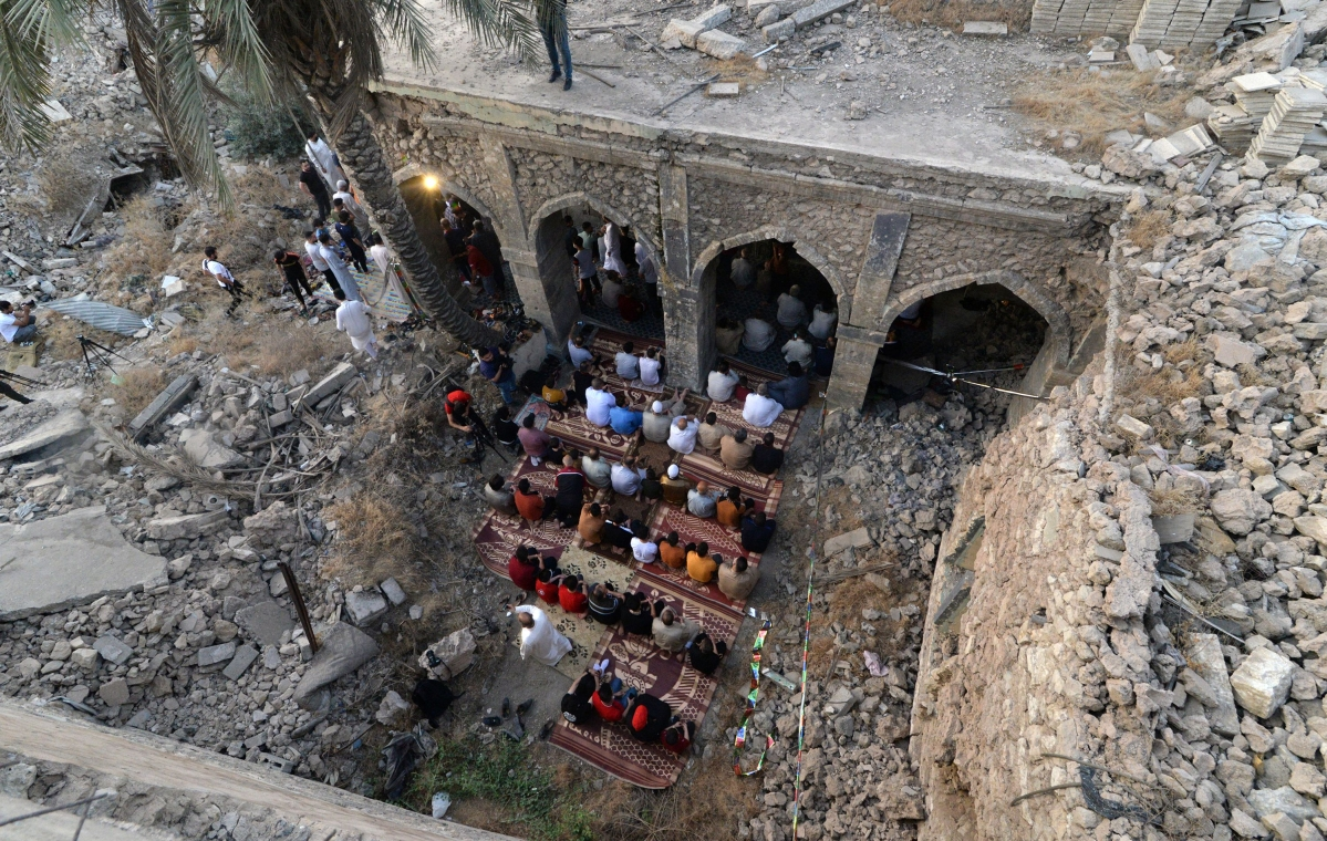 An aerial view shows Iraqi worshippers taking part in the Eid Al-Fitr prayer in the Old City of Mosul, in the courtyard of the damaged Umayad mosque, early on May 13, 2021, to mark the end of the Muslim holy month of Ramadan.