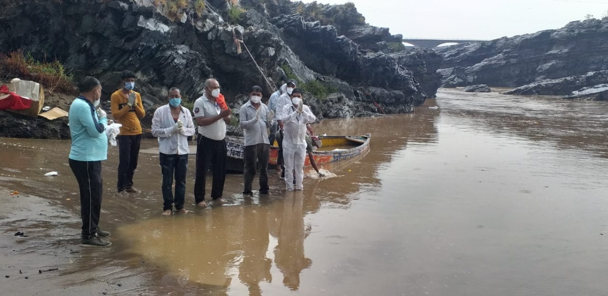 Municipal corporation employees offering mortal remains in the Narmada river at Barman Ghat in Narsinghpur district on Tuesday