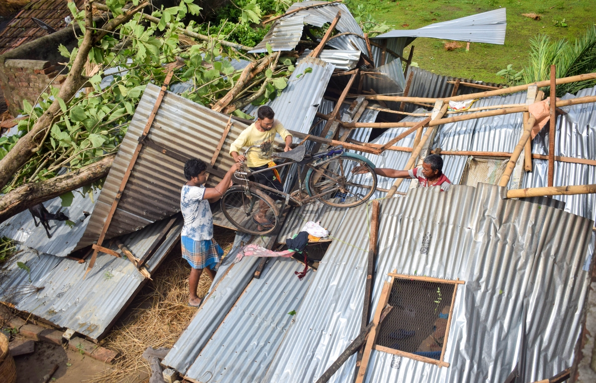 A view of an uprooted tree and damaged house after cyclone Yaas, at Santipur in Nadia district, Thursday, May 27, 2021