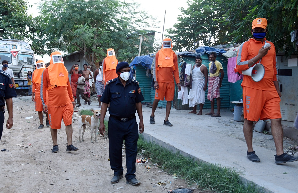 NDRF personnel making people aware ahead of Cyclone Yass, at Shalimar, in Howrah on Monday
