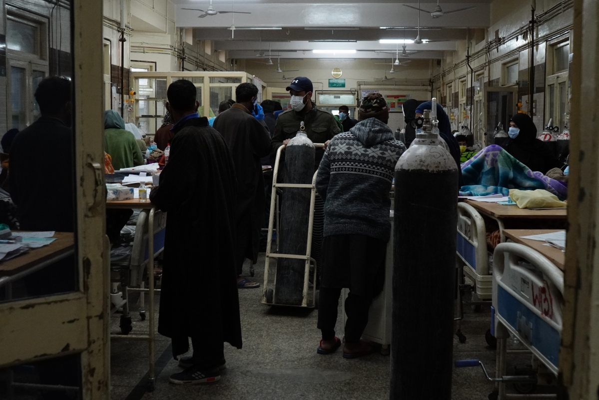 Relatives of COVID-19 patients carry oxygen cylinders to refill at SMHS Hospital in Srinagar, Kashmir.