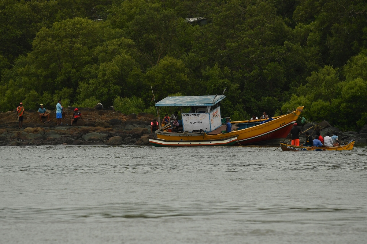 Fishermen are seen next to a fishing dhow that was thrown onto the rocks by strong winds caused by the impending cyclone Tauktae at a fishing village off the city coast in Mumbai on May 16, 2021.