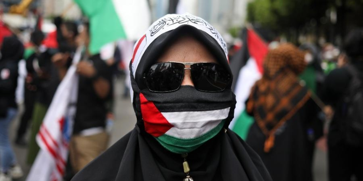 A Muslim woman wears a face mask with the colors of Palestinian flag during a rally condemning Israeli attacks on the Palestinians in Jakarta, Indonesia.