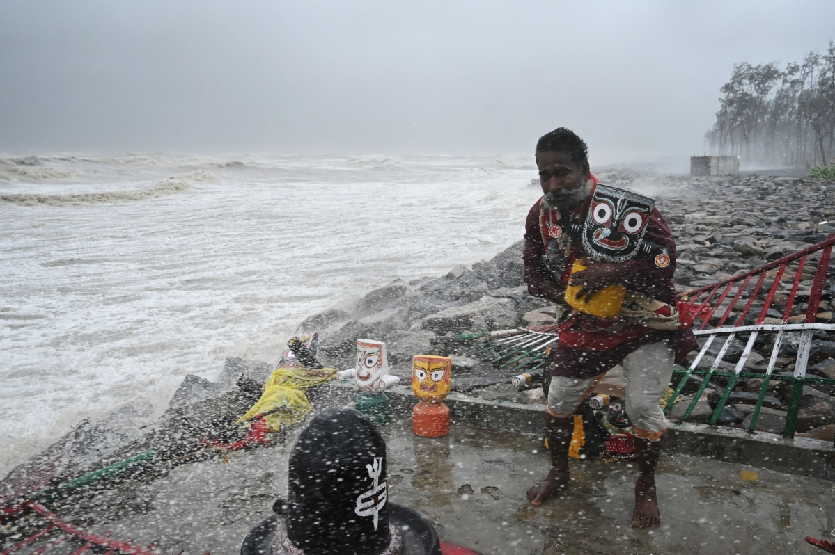 A Hindu priest removes an idol of Lord Jagannath from a seafront temple to a safer place while strong winds batter Balasore district in Odisha state on May 26, 2021 as Cyclone Yaas barrels towards Indias eastern coast in the Bay of Bengal.