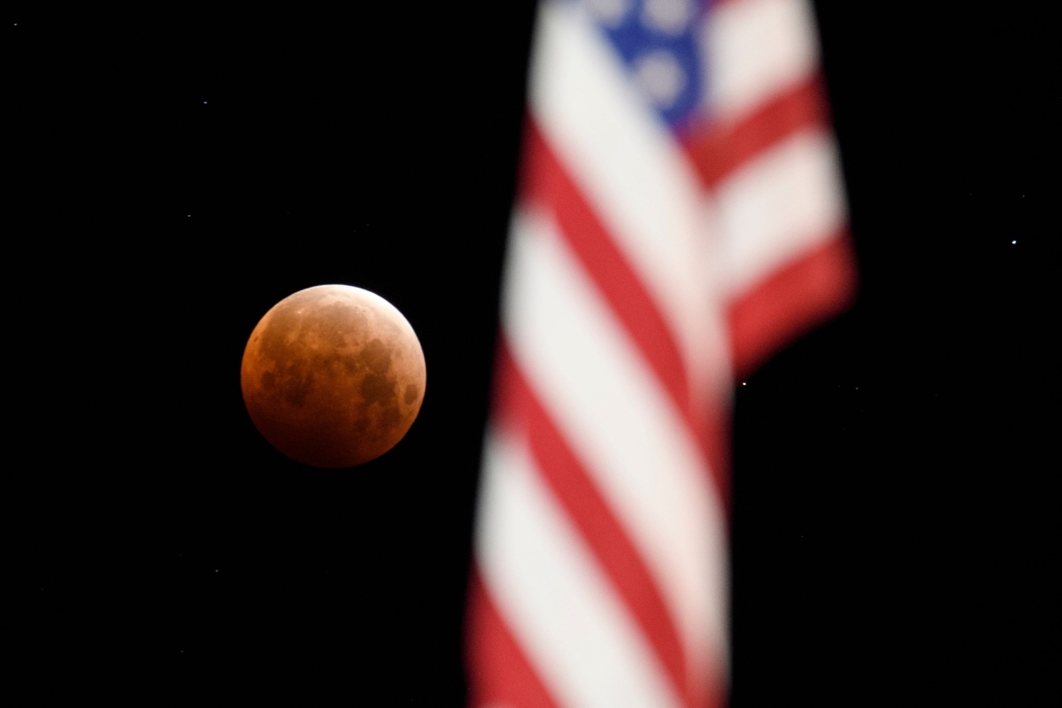 """A full moon is seen framed with a US flag during totality of a total lunar eclipse as the moon enters Earths shadow for a """"Super Blood Moon"""" on May 26, 2021 in Chico, California."""