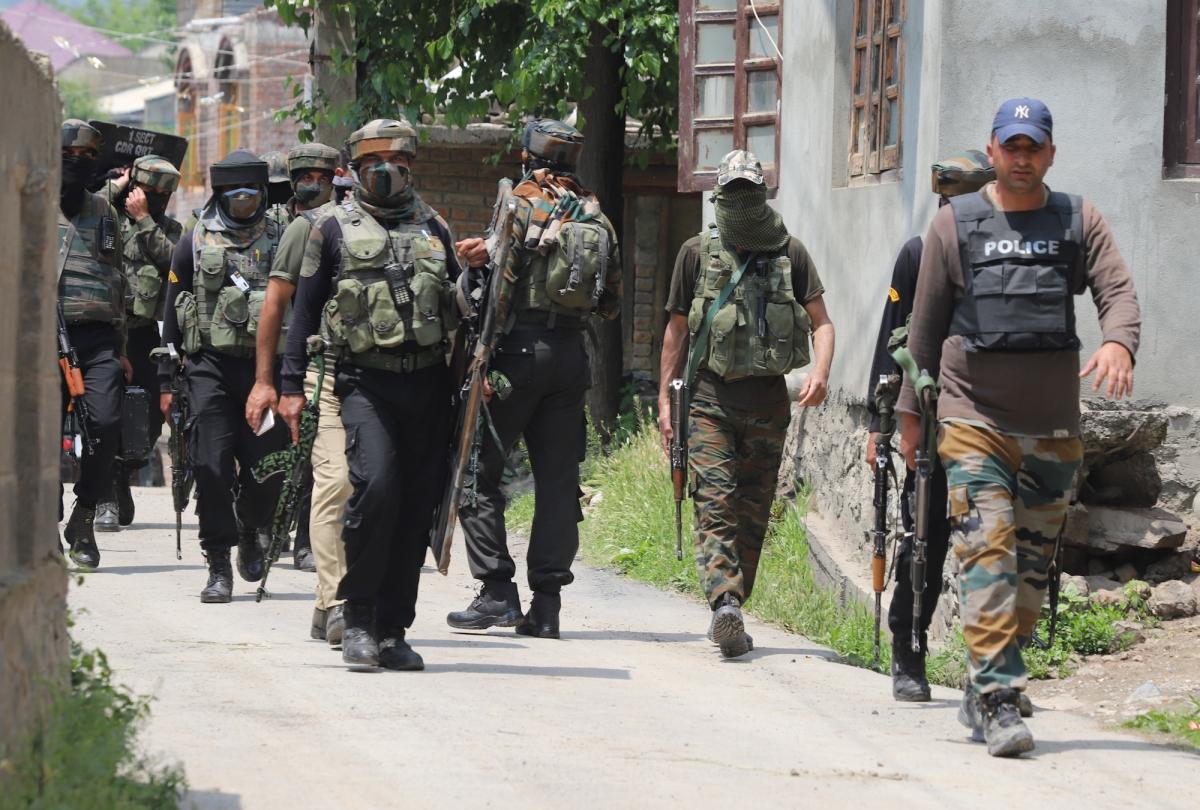 Policemen walk near the gun-battle site on the outskirts of Srinagar, Kashmir on May 17, 2021.