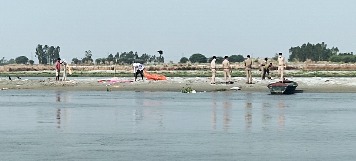 Bodies of suspected Covid patients found in the Ganga being cremated by the administration, in Unnao, Uttar Pradesh