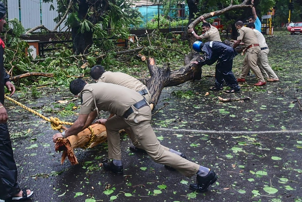 Police personnel clear fallen trees from a road following severe cyclonic storm Tauktae, at Panjim in Goa on May 16, 2021.