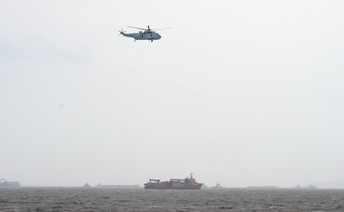 A helicopter flys over a ship anchored in the rough Arabian Sea near Mumbai