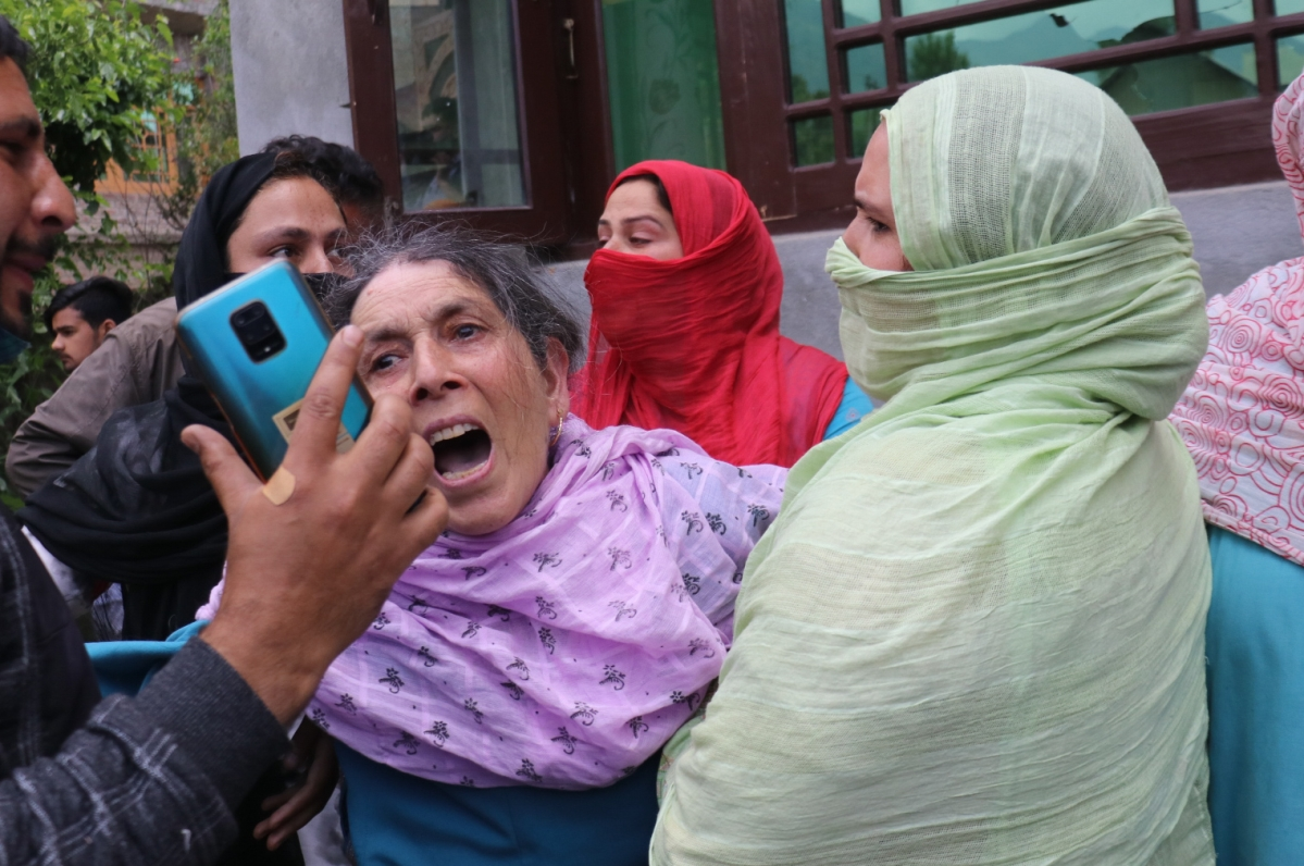 A civilian woman wails near the site of the encounter on the outskirts of Srinagar, Kashmir on May 17, 2021.