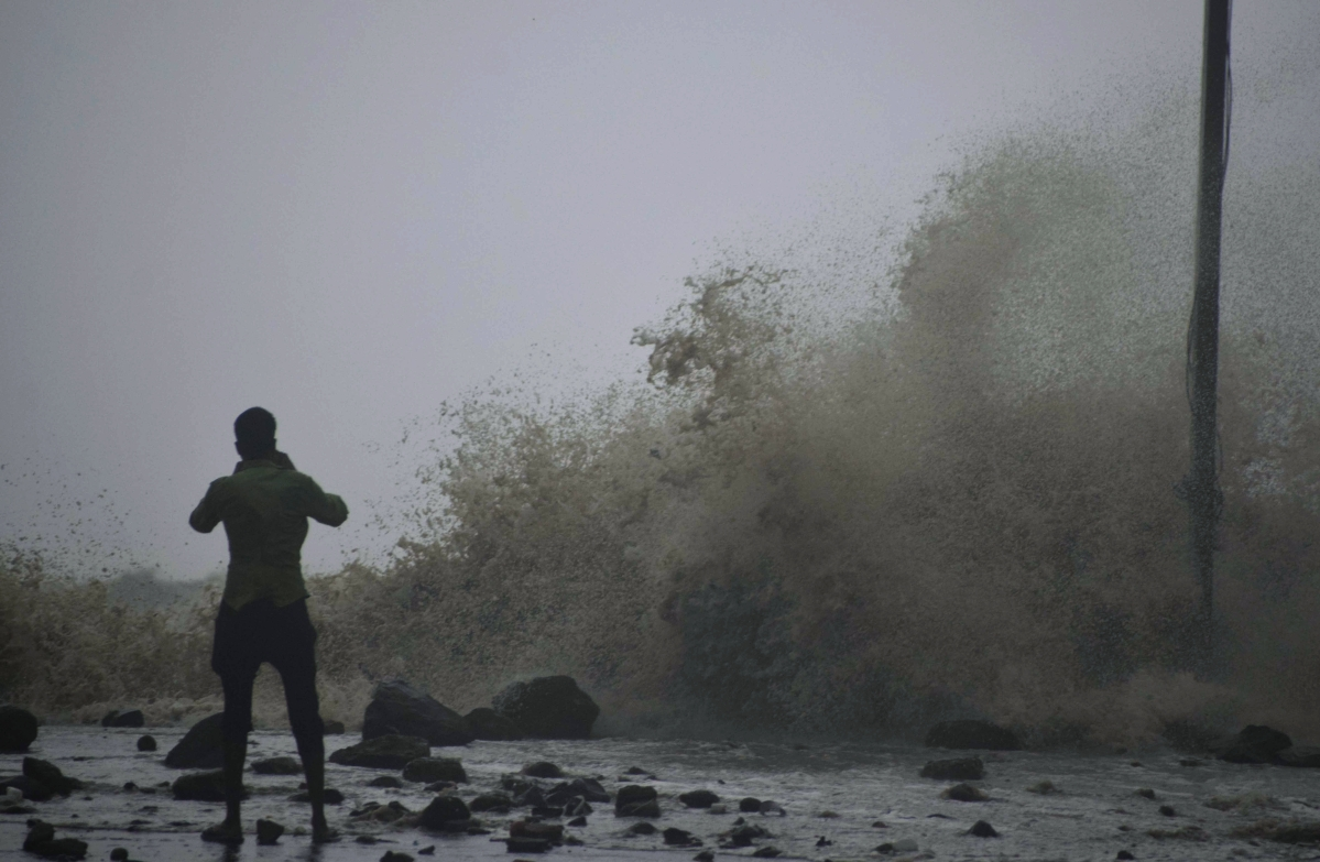 A man stands next to the turbulent sea with strong winds on Digha Sea Beach ahead of cyclone Yaas, in East Medinipur on Wednesday.