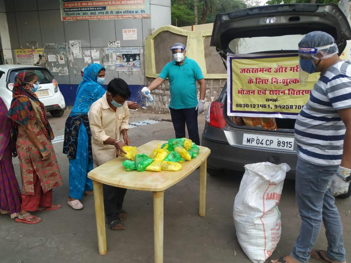 Organisation members distribute food packets to poor people.