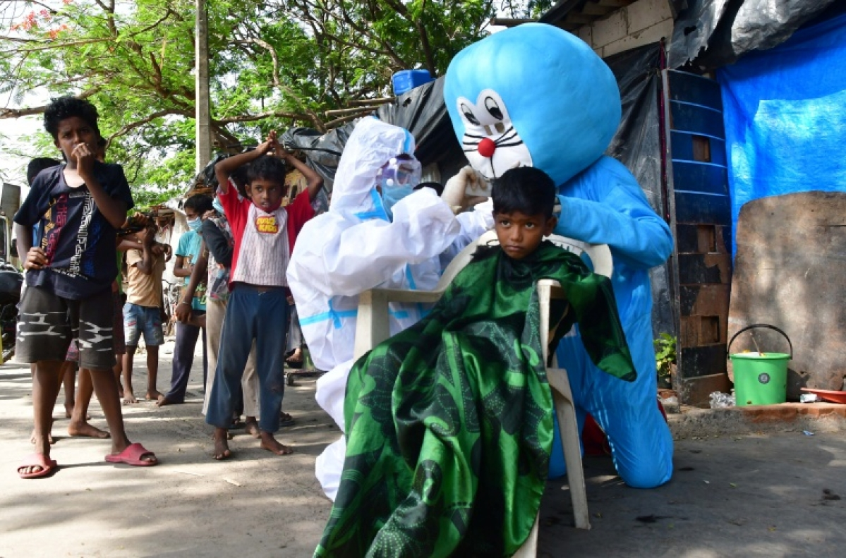 Barber giving haircut to kids while a man dressed as Doraemon accompanies him
