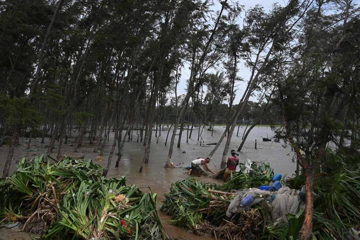 Fishermen collect damaged fishing nets after Cyclone Yaas hit Indias eastern coast in the Bay of Bengal, at a beach in Digha, some 190 km from Kolkata on May 27, 2021.