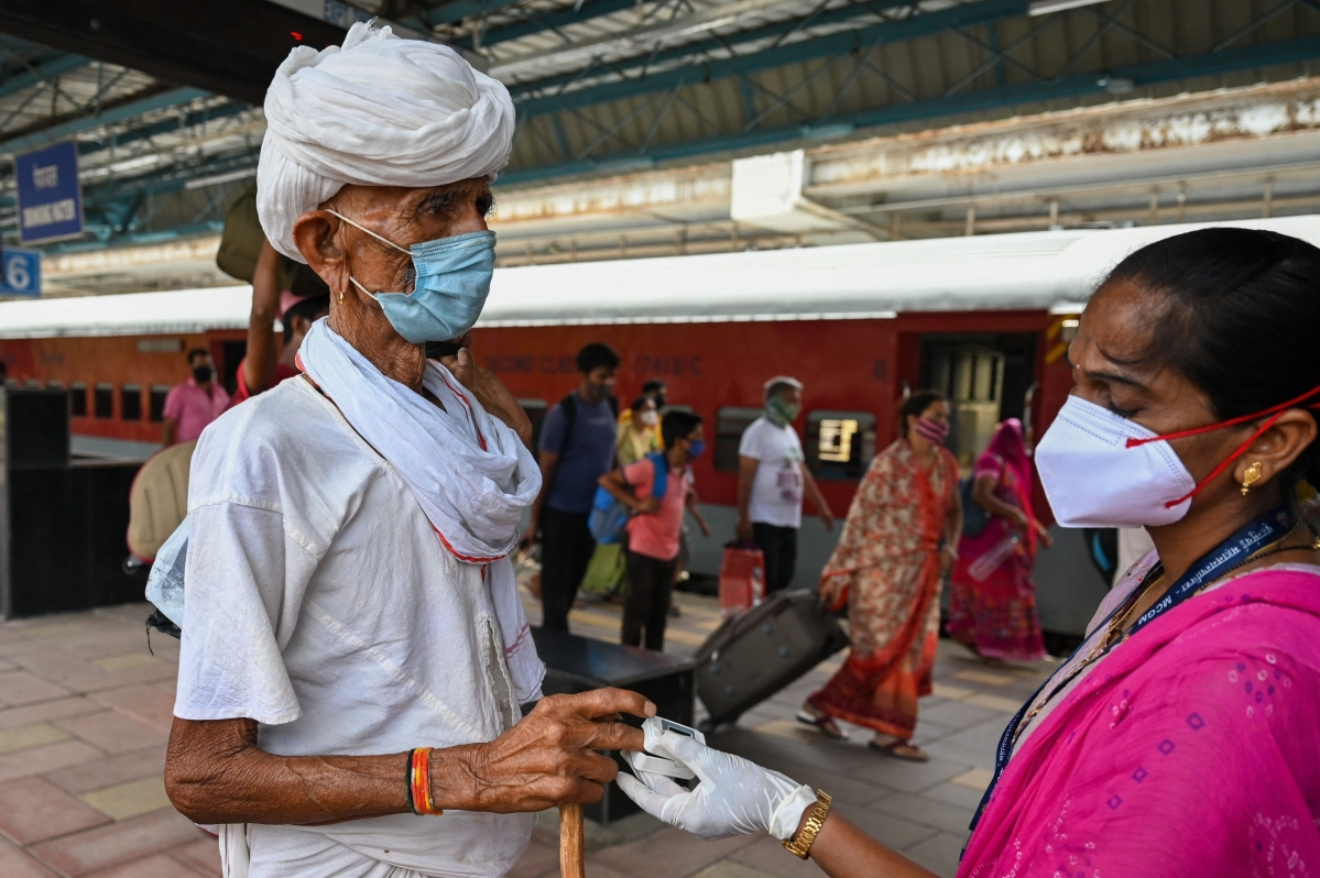 A health worker checks the oxygen saturation of a passenger during a screening to check for Covid-19 coronavirus symptoms on passengers after arriving at a railway platform on a long distance train, in Mumbai on May 27, 2021.