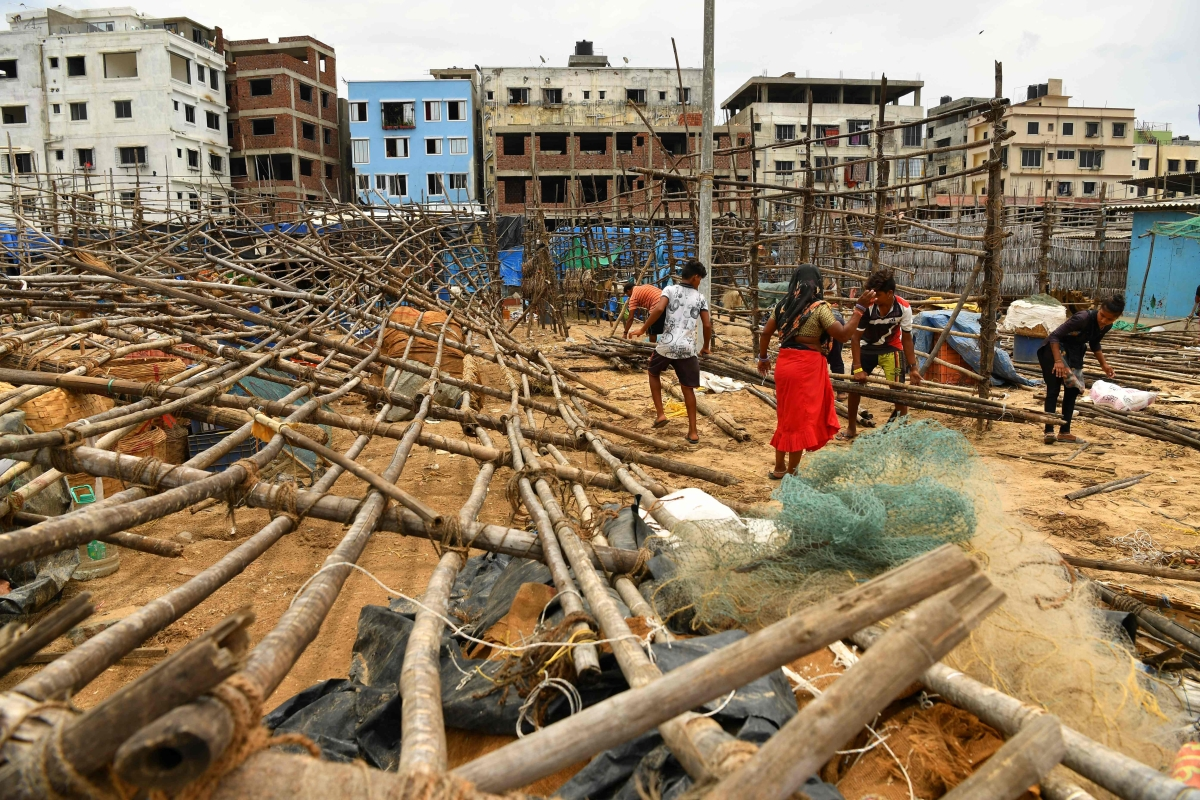 Fisherfolk mend bamboo racks being used to dry fishes after they were brought down by strong winds caused by the impending cyclone Tauktae at a fishing village off the city coast in Mumbai on May 16, 2021.