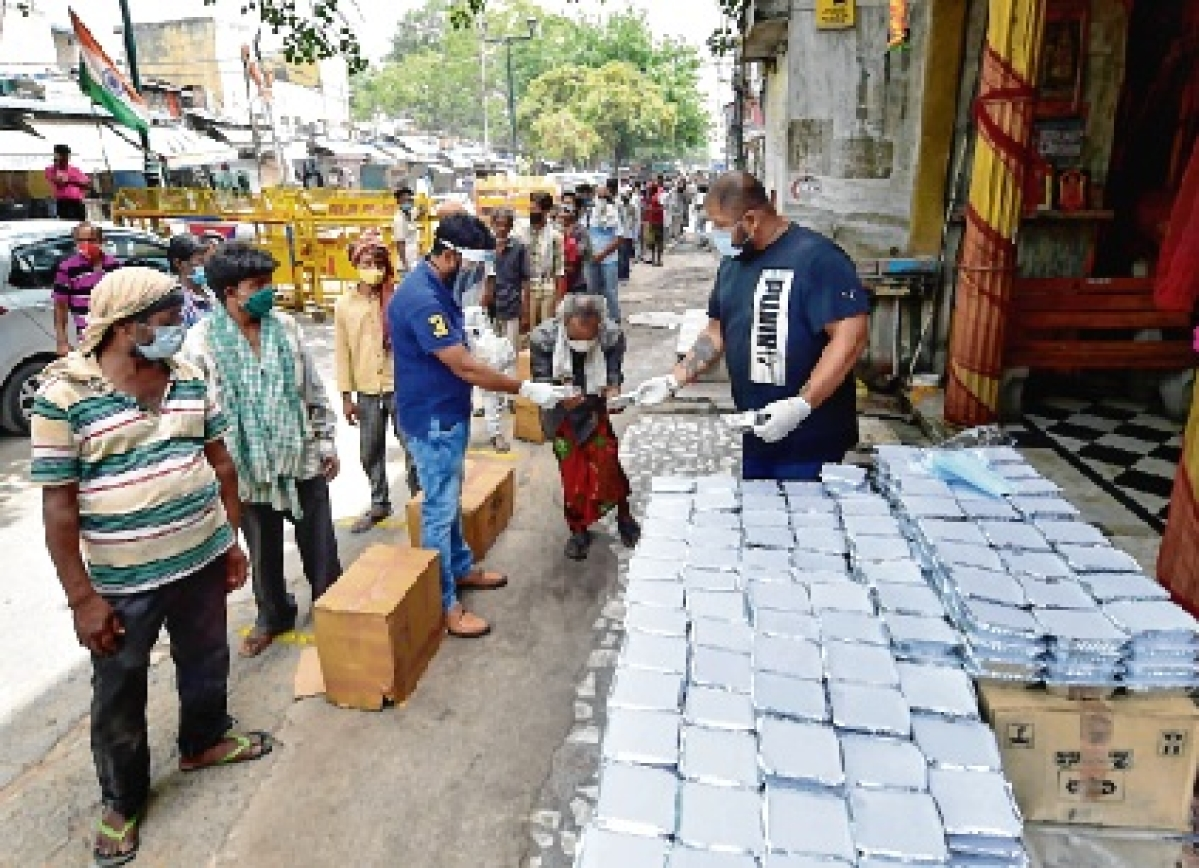 Former international powerlifting champion and national-level shooter Gaurav  Sharma distributes food among the homeless in New Delhi on Sunday.