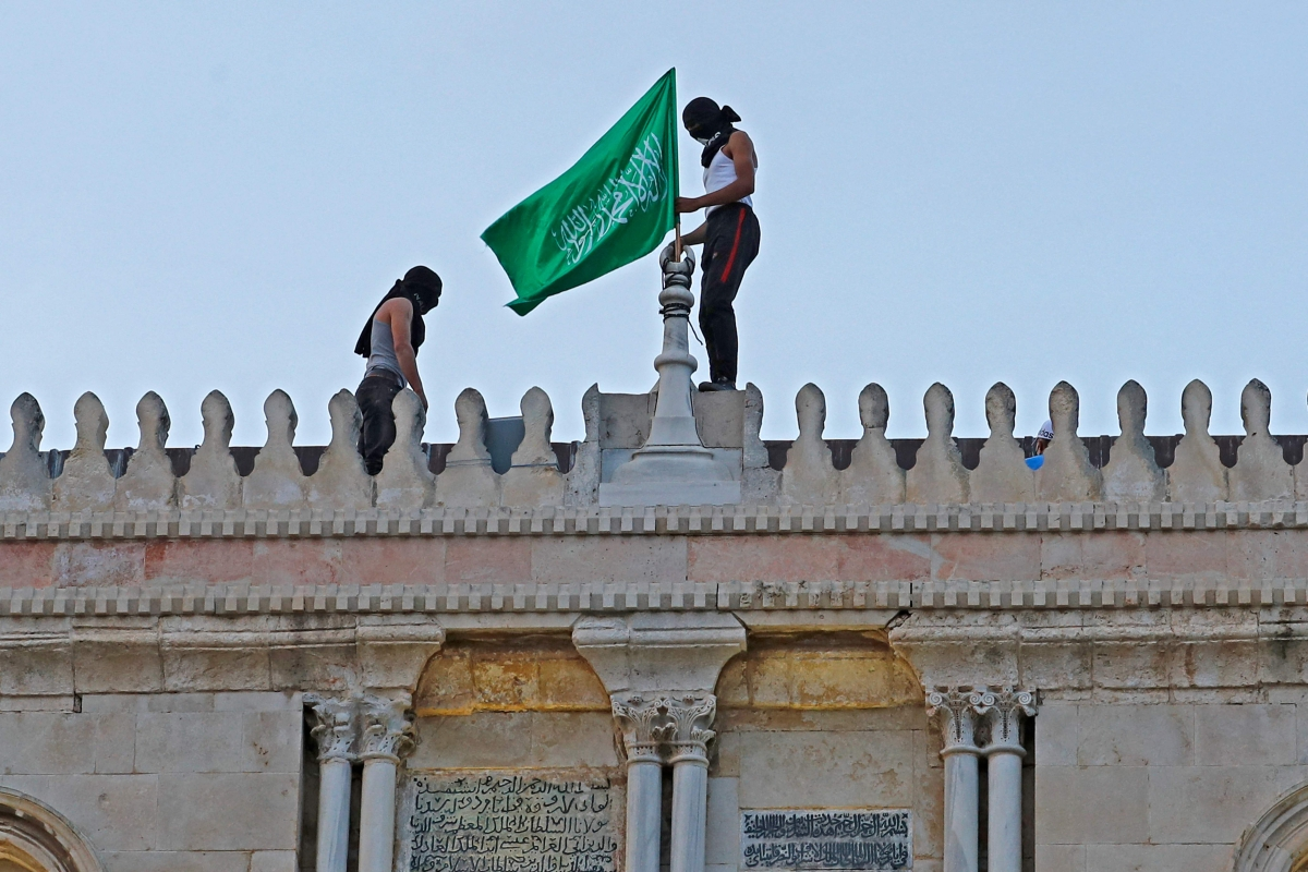 Palestinians place the Hamas movement flag atop Jerusalems al-Aqsa mosque on May 10, 2021, amid clashes with Israeli scurity forces ahead of a planned march to commemorate Israels takeover of Jerusalem in the 1967 Six-Day War.