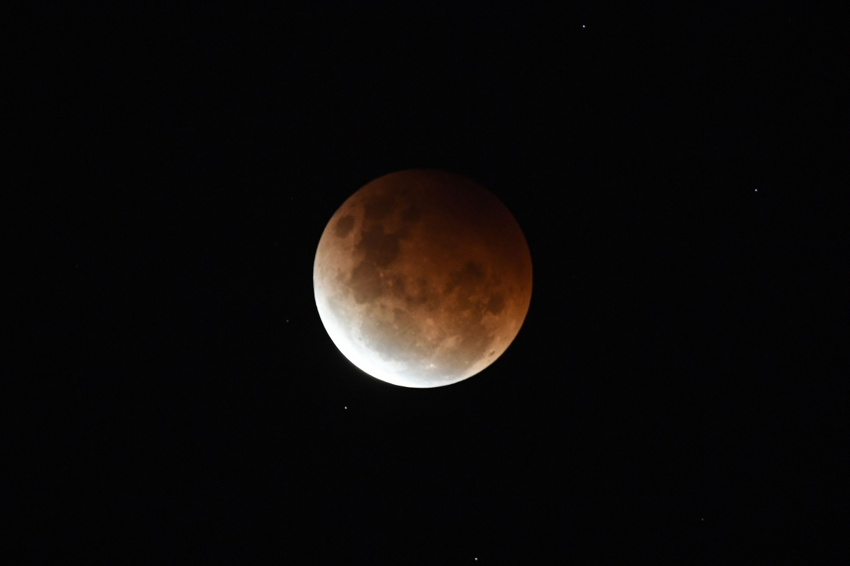 """The full moon is seen during the partial eclipse in Sydney on May 26, 2021 as stargazers across the Pacific are casting their eyes skyward to witness a rare """"Super Blood Moon""""."""