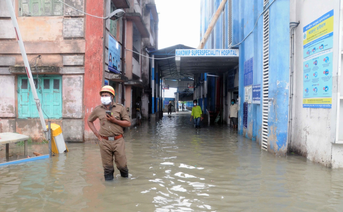 A security personnel seen standing on a water logged road outside Kakdwip Hospital after the landfall of cyclone Yaas, at Kakdwip in South 24 Paragnas, Wednesday, May 26, 2021.