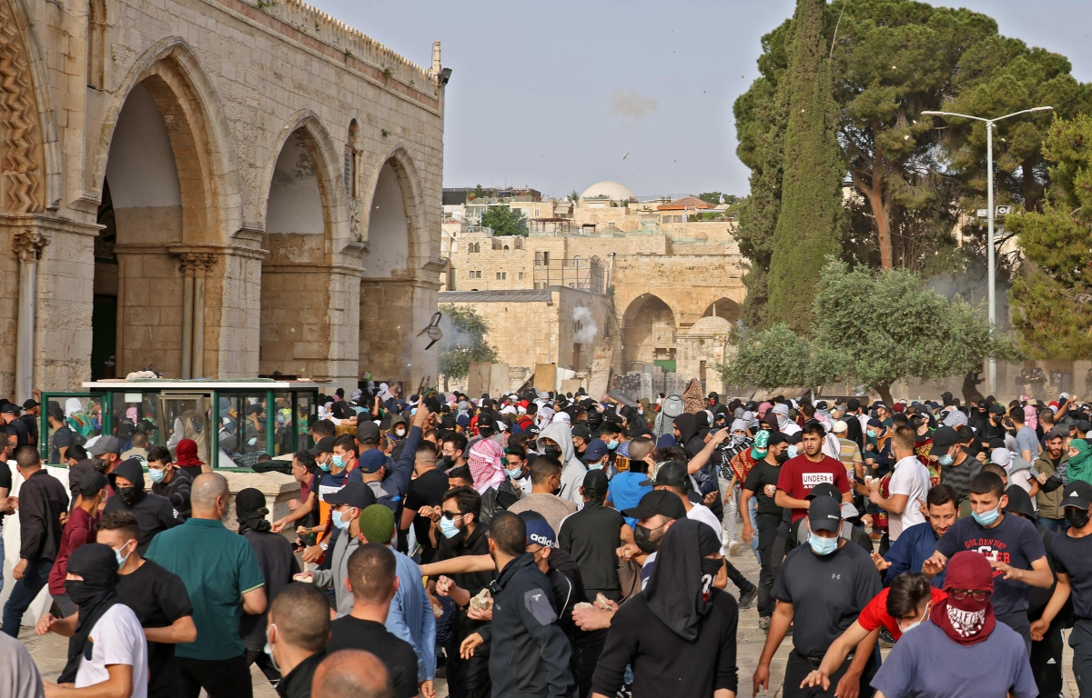 Palestinians run for cover from tear gas fired by Israeli security forces at Jerusalems Al-Aqsa mosque compound on May 10, 2021, ahead of a planned march to commemorate Israels takeover of Jerusalem in the 1967 Six-Day War.