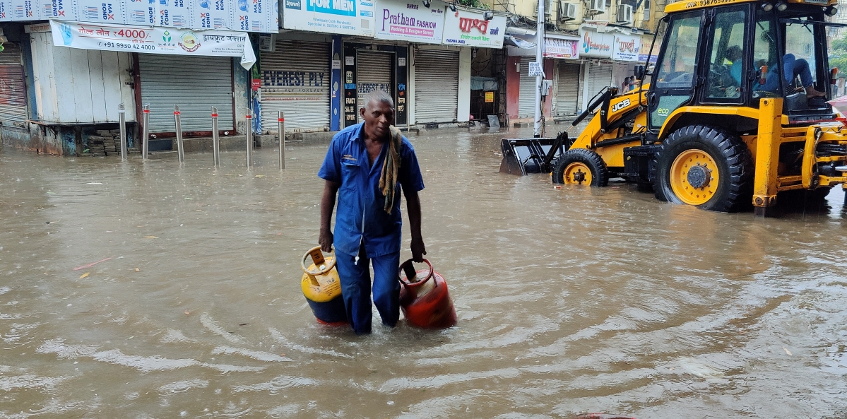 A man wades through a waterlogged street after heavy rainfall in view of Cyclone Tauktae, in Mumbai ?on Monday.