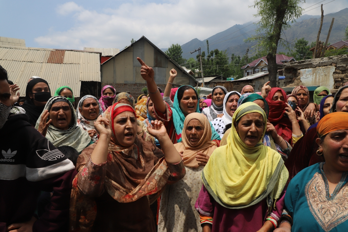 Kashmiri Muslim women shout anti-India slogans near the house damaged during the encounter on the outskirts of Srinagar, Kashmir on May 17, 2021.