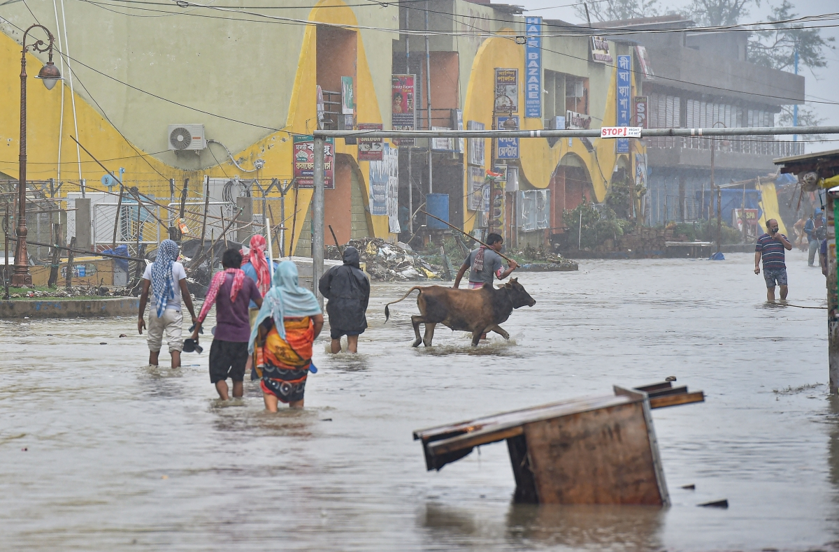 Digha: Pedestrians wade through a flooded road during landfall of cyclone Yaas at Digha in East Midnapore district, Wednesay, May 26, 2021.