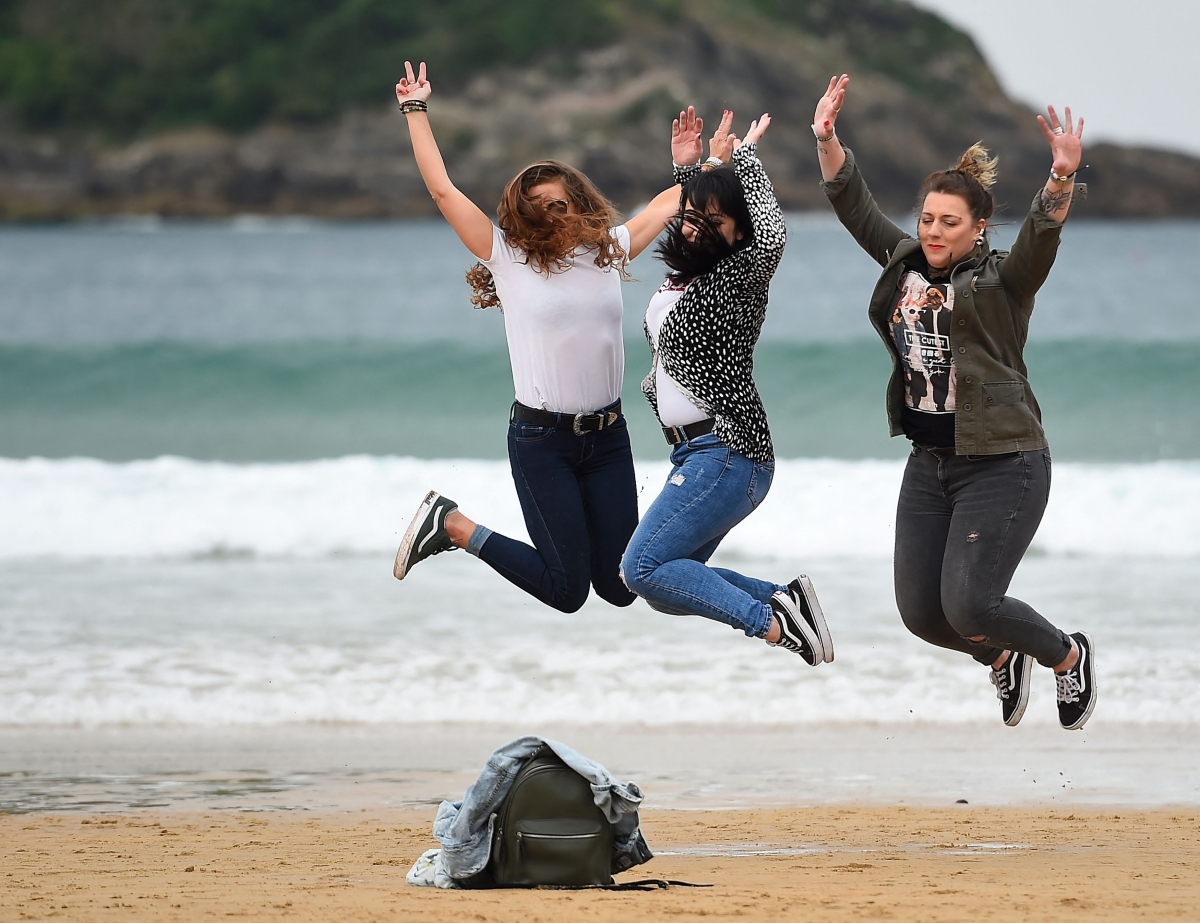Three women jump for a photo on La Concha beach in San Sebastian, on May 9, 2021. - Spain has lifted a state of emergency in place since October 2020 to fight the pandemic, allowing Spaniards to travel between regions for the first time in months.