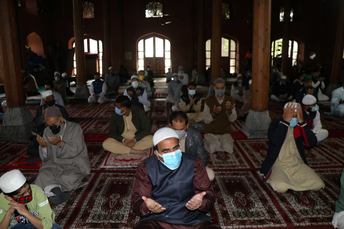 Worshippers wearing protective face masks offer Eid ul-Fitr prayers inside a local mosque to help prevent the spread of Coronavirus in Srinagar, Kashmir.