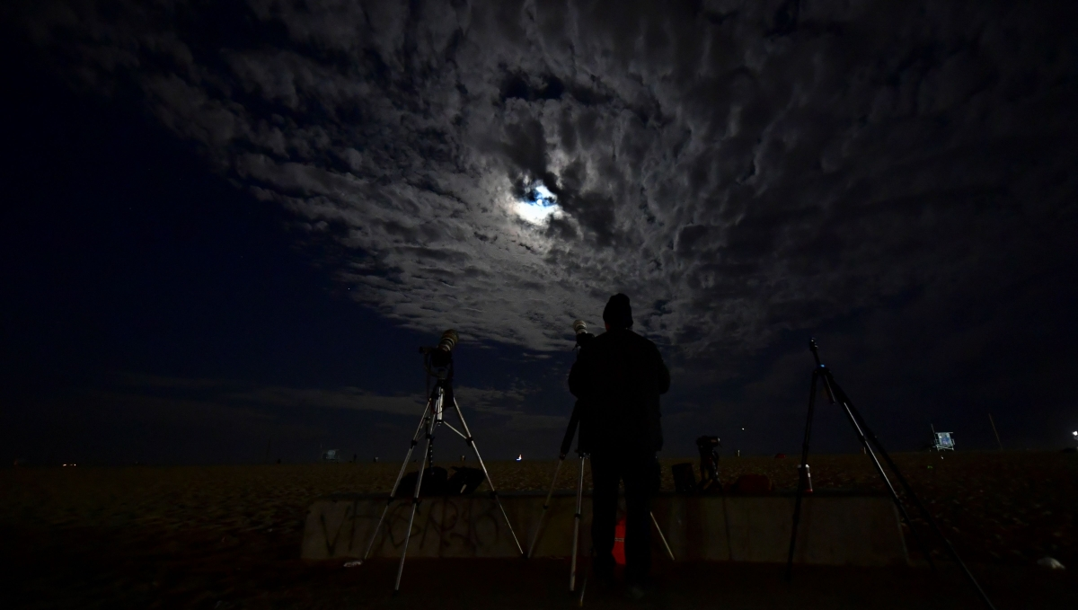 """Clouds cover the Moon as a photographer views it from Santa Monica, California ahead of a total lunar eclipse early on May 26, 2021, as stargazers across the Pacific are casting their eyes skyward to witness a rare """"Super Blood Moon""""."""