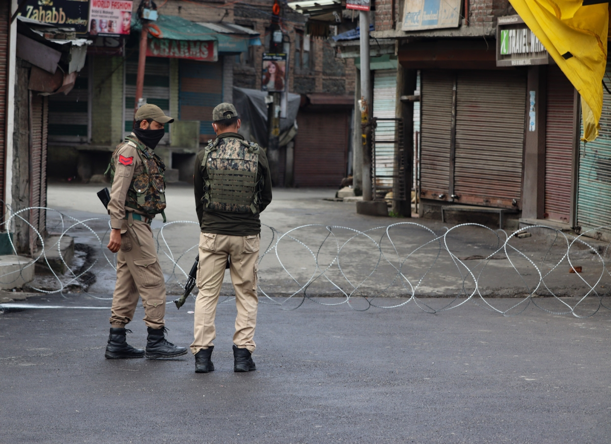 Security personnel stand guard at a deserted street as strict curfew has been imposed amid concerns over the spread of Coronavirus during the Muslim festival of Eid ul-Fitr in Srinagar, Kashmir.