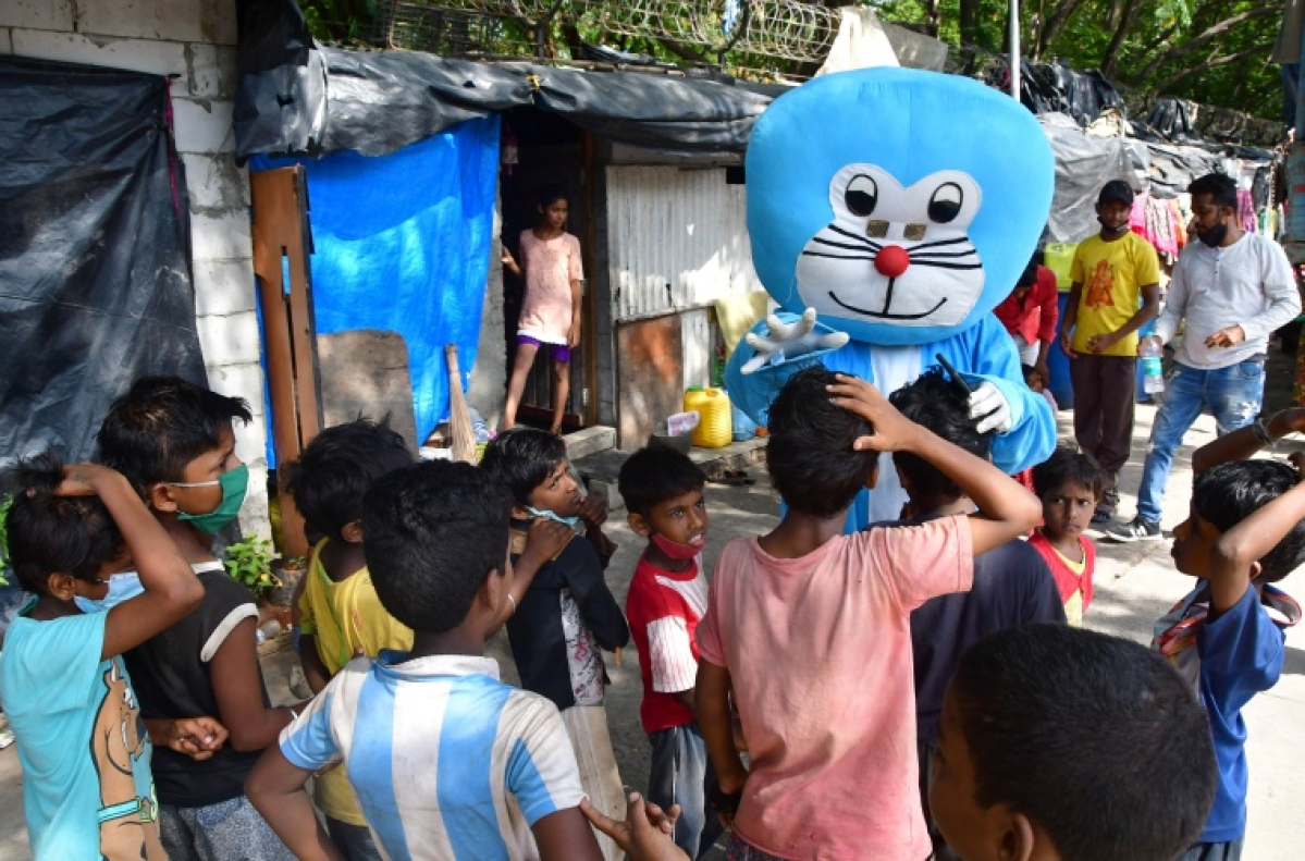 Man dressed as Doraemon talks to kids in slum