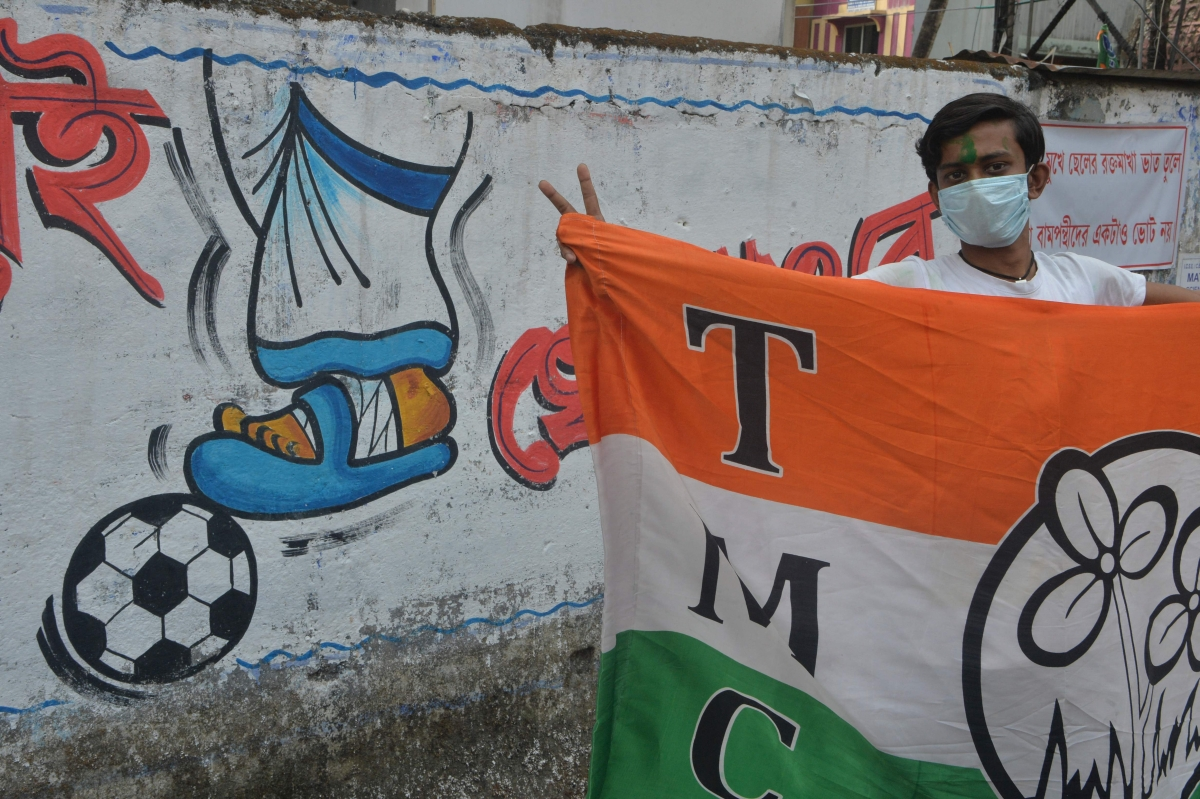 Indian supporters of the All India Trinamool Congress (AITC) celebrate the party's lead in front of a mural depicting the injured foot of AITCs leader Mamata Banerjee during the ongoing counting process of the West Bengal legislative assembly election, in Siliguri on May 2, 2021.