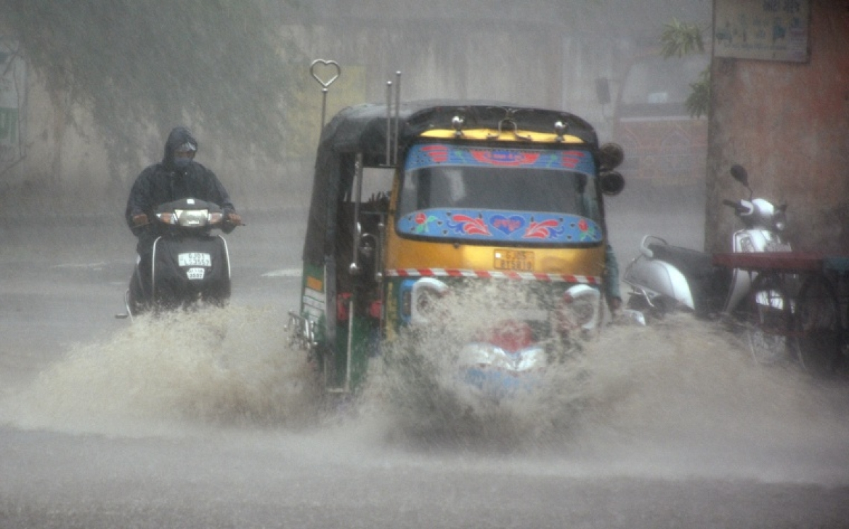 Commuters wade through a waterlogged street during heavy rainfall due to cyclone tauktae, in Surat on Tuesday