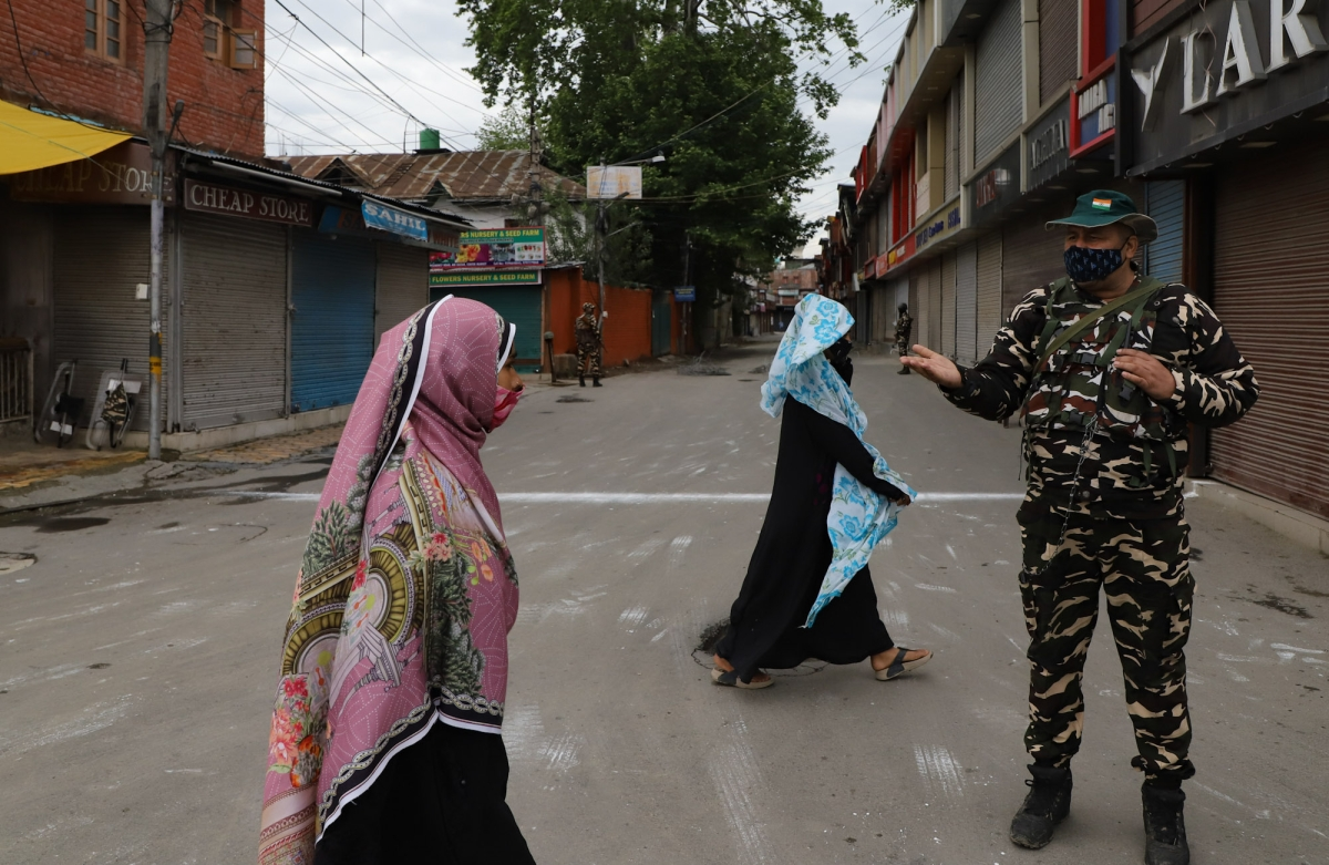 Kashmiri women walk past security personnel on the day of the Muslim festival of Eid ul-Fitr as strict curfew has been imposed amid concerns over the spread of Coronavirus in Srinagar, Kashmir.