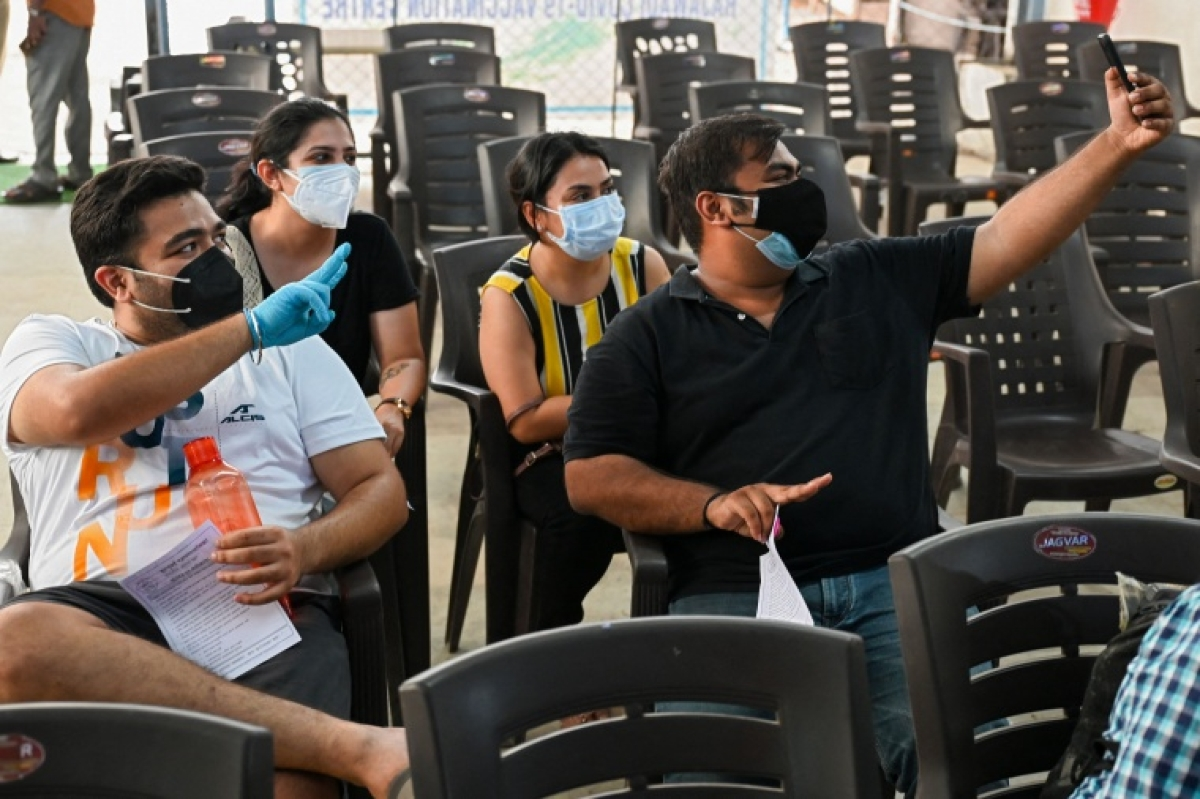 Youths take pictures as they wait for their turn to get inoculated with a dose of Covishield vaccine against the Covid-19 coronavirus at the Rajawadi Hospital in Mumbai on May 1, 2021, during the first day of Indias vaccination drive to all adults.