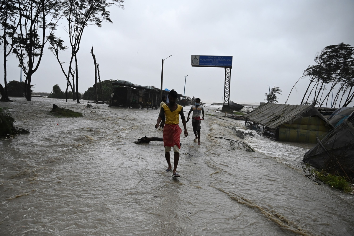 Residents walk in a beachfront area as sea water reaches a nearby road while Cyclone Yaas barrels towards Indias eastern coast in the Bay of Bengal, in Digha on May 26, 2021.