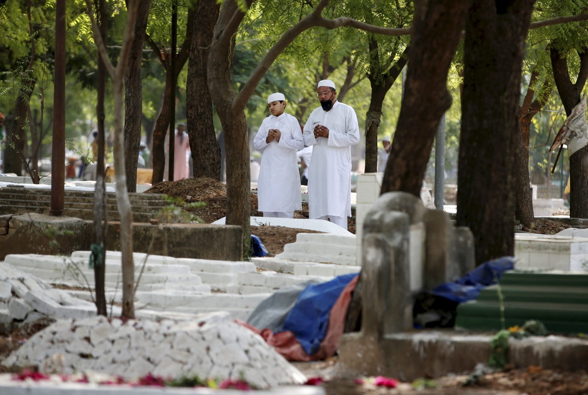 Muslims offer prayers next to the graves of their relatives on the occasion of Eid ul-Fitr, at a graveyard in Ahmedabad, Friday, May 14, 2021.