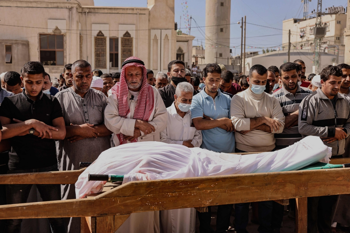 Mourners recite a prayer over the body of Majd Abu Saadahthe, a Palestinian killed in an Israeli airstike, during his funeral in the town of Khan Yunis in the southern Gaza Strip, on May 12, 2021. - Israeli air raids in the Gaza Strip have hit the homes of high-ranking members of the Hamas militant group, the military said Wednesday, with the territorys police headquarters also targeted.