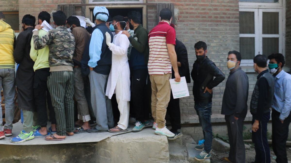 Family members of COVID-19 patients wait outside an oxygen-filling center to refill their empty cylinders as demand for the gas rises due to spike in Coronovirus cases in Srinagar, Kashmir.