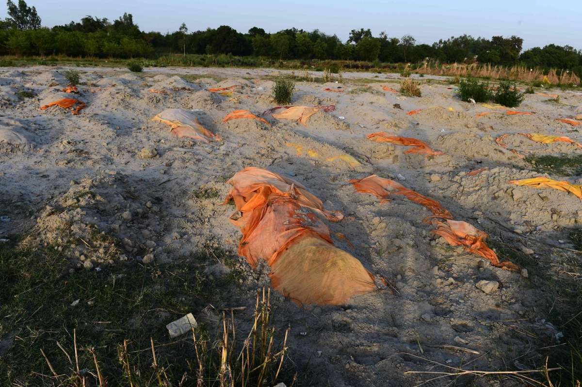 Bodies of suspected Covid-19 coronavirus victims are seen partially buried in the sand near a cremation ground on the banks of Ganges River in Rautapur Ganga Ghat, in Unnao