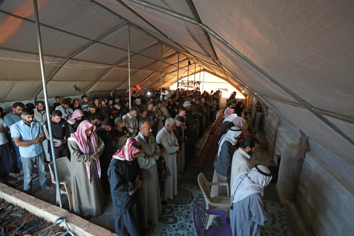 Displaced Syrians gather to pray inside a tent at the al-Tah camp for internally displaced persons (IDP) in Syrias rebel-held northwestern province of Idlib on May 13, 2021, on the first day of the Eid al-Fitr holiday, which marks the end of the holy fasting month of Ramadan.