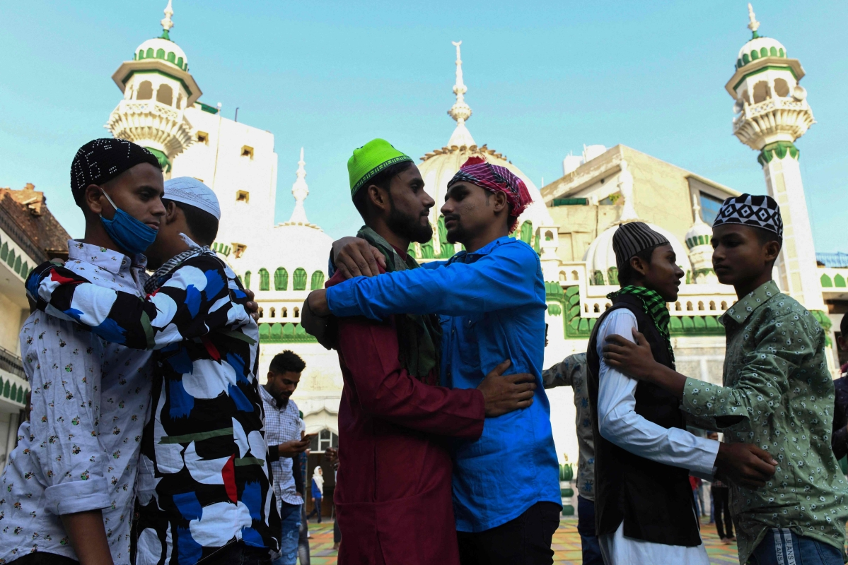 Muslim devotees hug each other after offering a special prayer on the occasion of Eid ul-Fitr festival, which marks the end of Islamic holy fasting month of Ramadan, at the Jama Masjid Khairuddin amid the coronavirus pandemic in Amritsar on May 14, 2021.