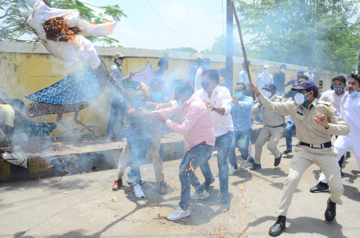 Policeman tries to snatch the CM's effigy from a Youth Congress worker near Chamunda Mata Mandir Chouraha in Ujjain on Friday.